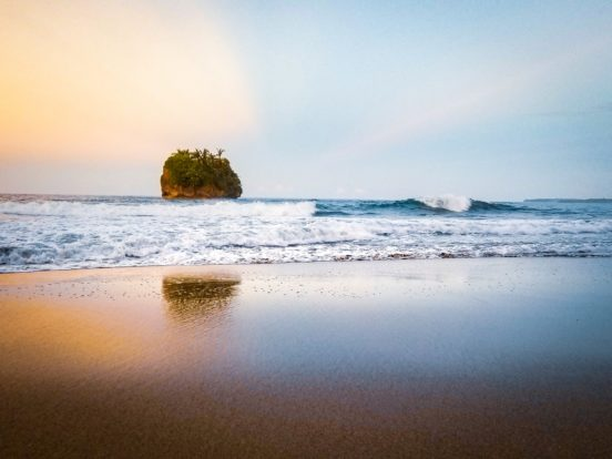 sunset at a Costa Rican beach with a rock in the sea