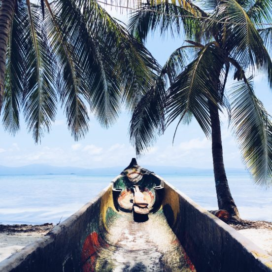 vintage canoe on a tropical beach under palm trees with ocean view