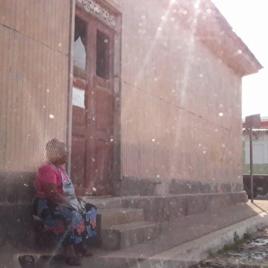 old woman sits on stairs in front of a house
