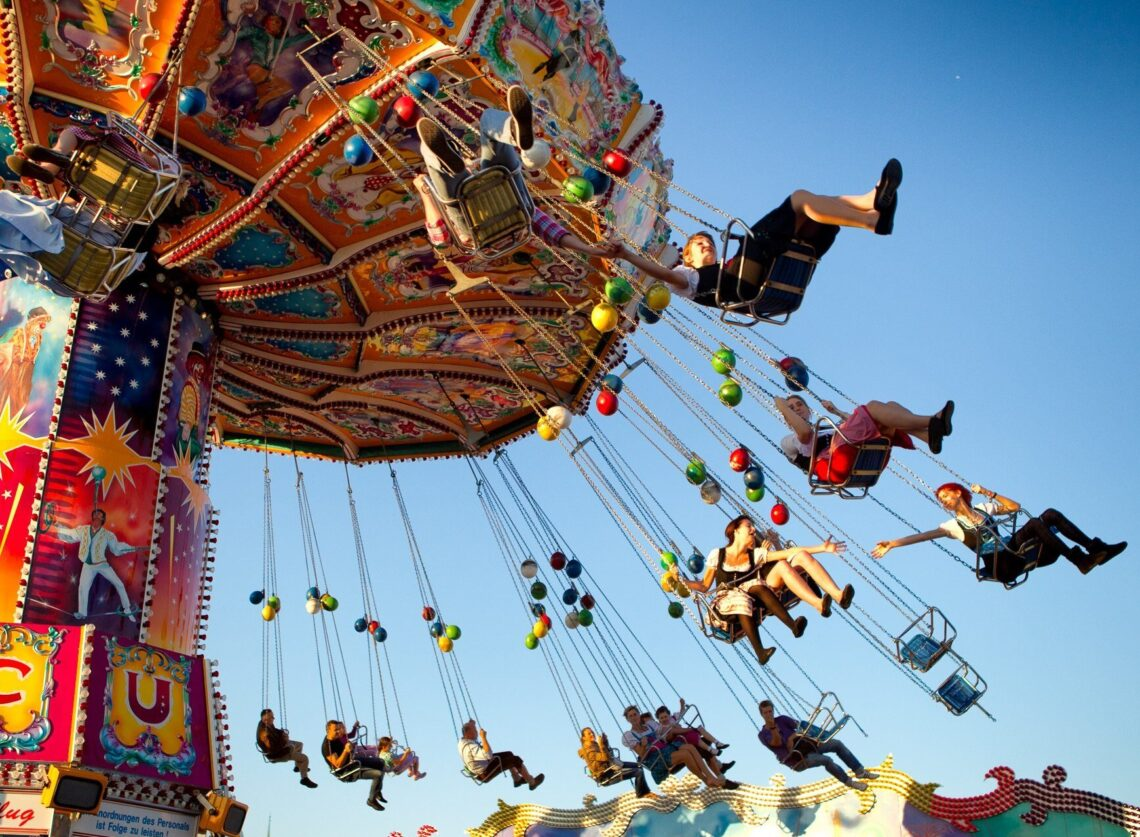 people in traditional Bavarian costumes enjoying themselves on a carrousel at Oktoberfest in Munich